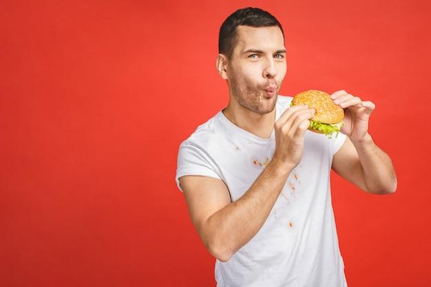 Homem barbudo faminto e engraçado comendo junk food