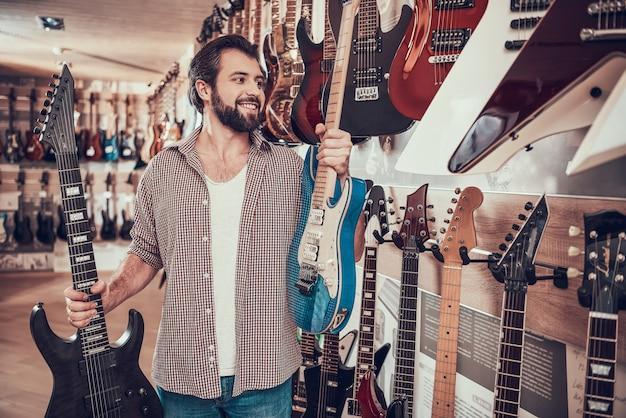 Homem barbudo faz escolha entre duas guitarras elétricas