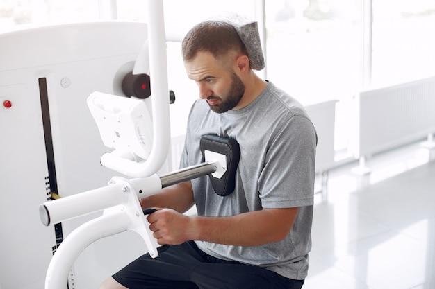 Homem barbudo fazendo reabilitação após lesão em clínica de fisioterapia