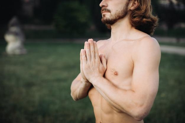 Homem barbudo fazendo yoga no parque verde