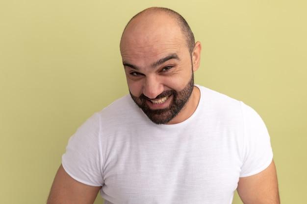 Homem barbudo feliz com camiseta branca e sorrindo maliciosamente em pé sobre a parede verde