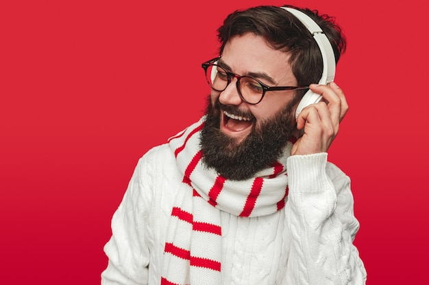 Homem barbudo feliz com suéter e lenço ouvindo música
