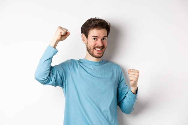 Homem barbudo feliz comemorando a vitória, levantando as mãos e triunfando, ganhando o prêmio e sorrindo com alegria, em pé sobre um fundo branco