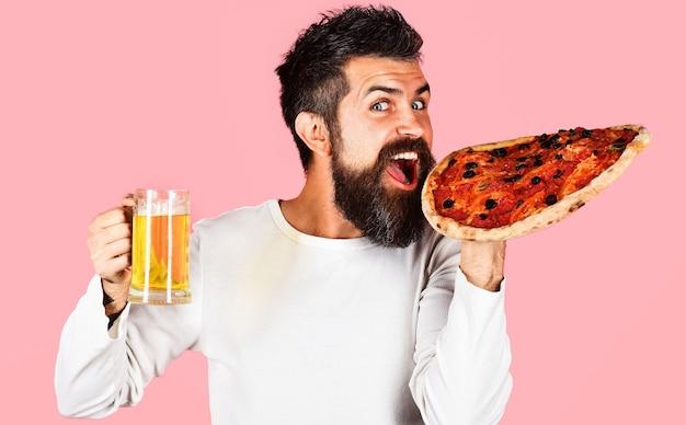 Homem barbudo feliz comendo pizza com cerveja. comida rápida, lanche, álcool.