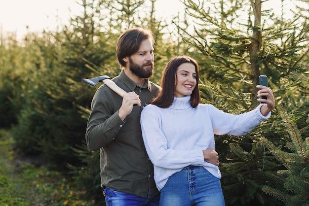 Homem barbudo feliz e a namorada bonita tirando foto de selfie na plantação de árvores de natal