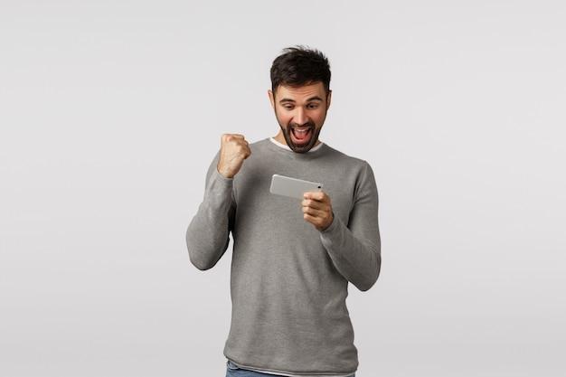 Homem barbudo feliz e alegre, animado, de suéter cinza, segurando o smartphone e o punho como celebração, digamos viva ou sim, vencendo o nível do jogo, veja as notícias no aplicativo