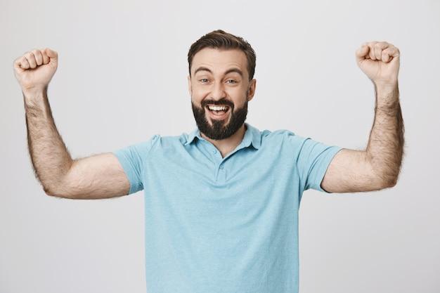 Homem barbudo feliz e satisfeito levantando as mãos, triunfando e comemorando
