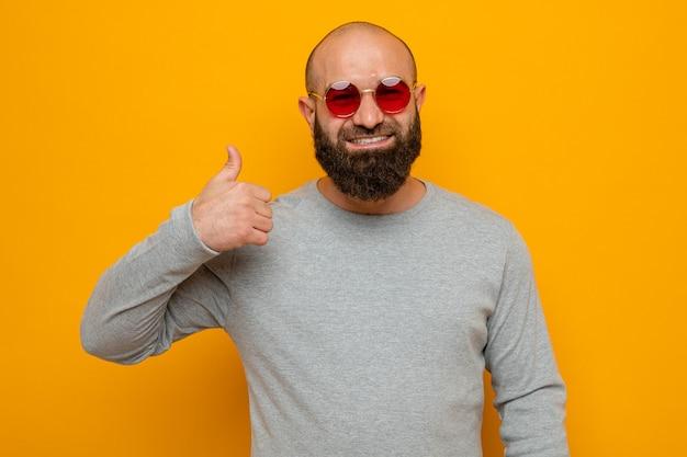 Homem barbudo feliz em moletom cinza de óculos vermelhos, sorrindo e mostrando o polegar para cima