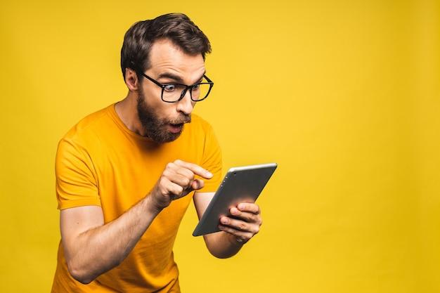Homem barbudo feliz espantado usando tablet digital, parecendo chocado com as notícias da mídia social, consumidor de comprador homem espantado surpreso com a vitória online isolada sobre fundo amarelo.