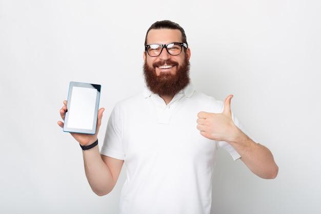 Homem barbudo feliz está mostrando a tela do tablet para a câmera enquanto mostra o polegar para cima gesto.