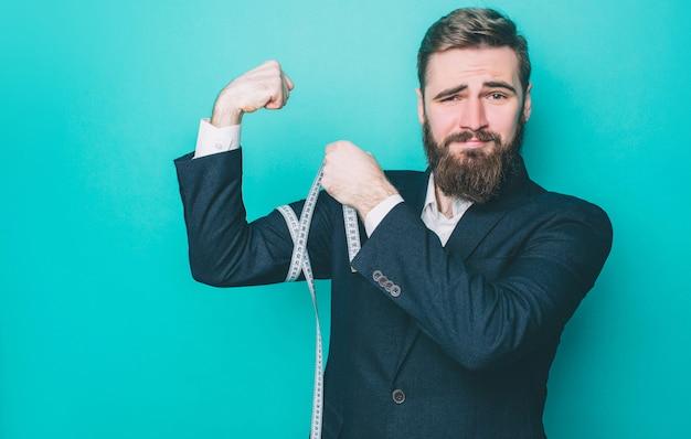 Homem barbudo forte e bem construído está medindo seu bíceps