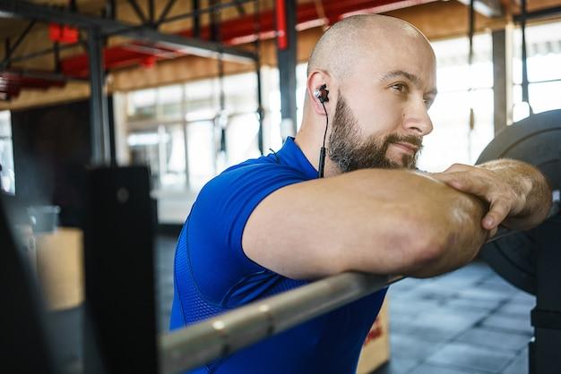 Homem barbudo forte em uma academia crossfit levantando um barbell.