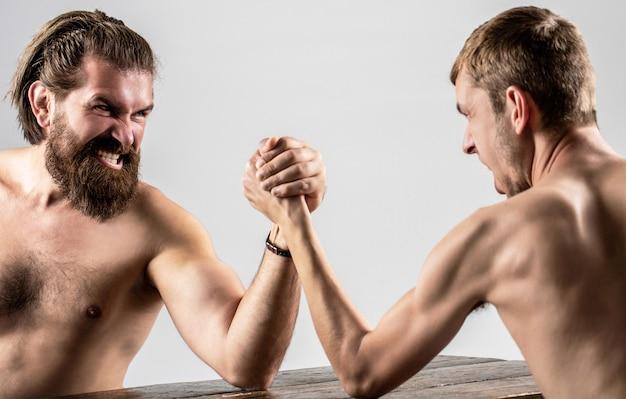 Homem barbudo fortemente musculoso lutando contra um homem fraco e franzino. luta de braços