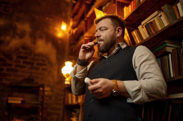 Homem barbudo fuma cigarro com porta-voz, estante e rico interior de escritório em segundo plano. cultura de fumar tabaco, sabor específico