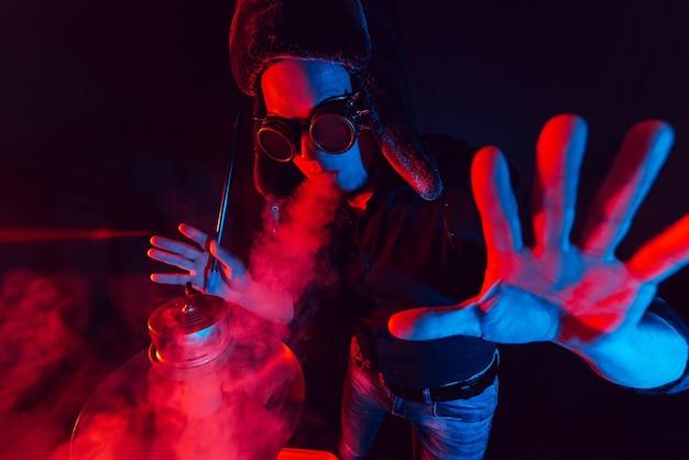 Homem barbudo fuma narguilé e exala uma nuvem de fumaça. retrato de um cara hipster de óculos e chapéu, descansando e relaxando em um bar shisha