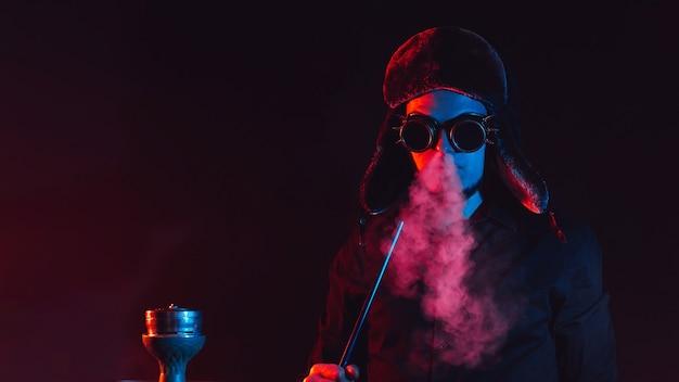 Homem barbudo fuma shisha em uma barra de narguilé e sopra uma nuvem de fumaça em um fundo escuro com iluminação neon