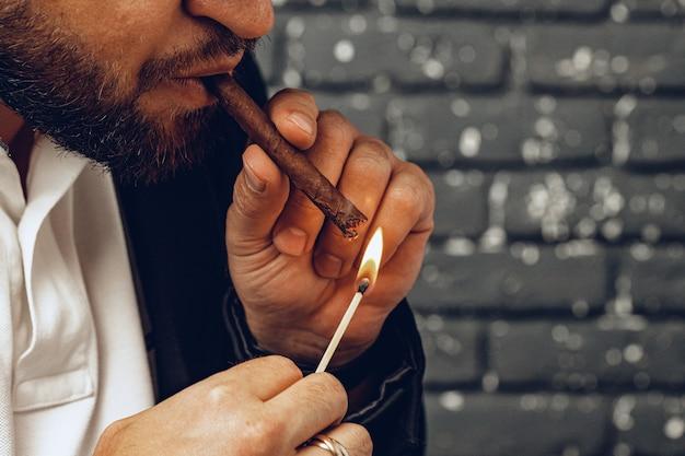 Homem barbudo fumando charuto contra uma parede de tijolos pretos close-up