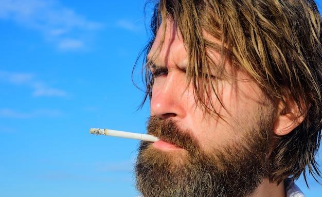 Homem barbudo fumando cigarro ao ar livre. cara brutal fumando tabaco. cannabis medicinal.