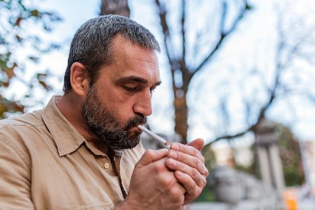 Homem barbudo fumando na rua