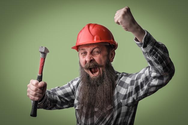 Homem barbudo gritando e segurando um martelo nas mãos