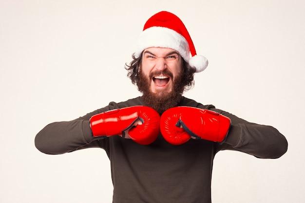 Homem barbudo gritando está de mãos dadas em luvas de boxe.
