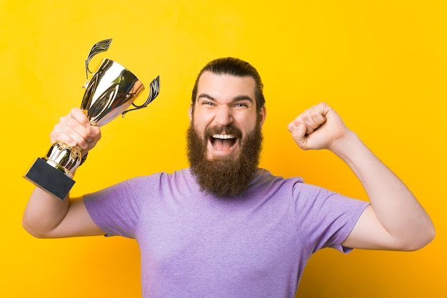 Homem barbudo gritando está fazendo o gesto de vencedor e segurando um troféu.