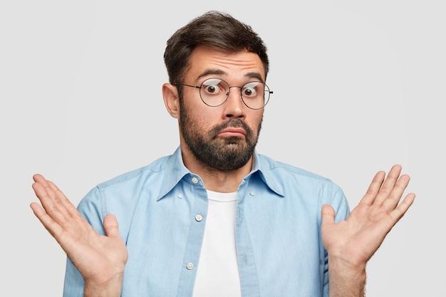 Homem barbudo hesitante com barba espessa, encolhe os ombros em perplexidade,