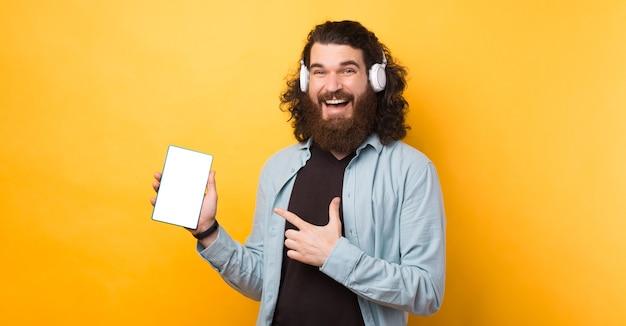 Homem barbudo hippie alegre usando fones de ouvido brancos sem fio e apontando para uma tela em branco no tablet