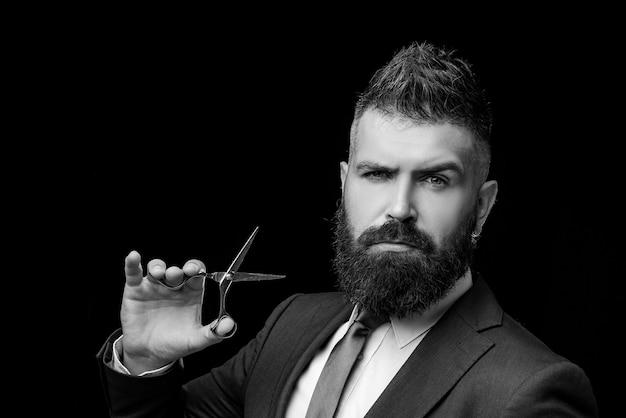 Homem barbudo, hippie barbudo. barba de homem estiloso. tesouras de barbeiro. barbearia vintage, barbear