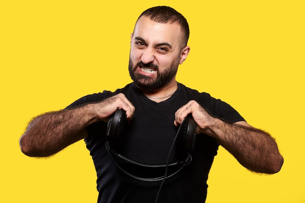 Homem barbudo hippie com fones de ouvido brincando e rasgando fio amarelo