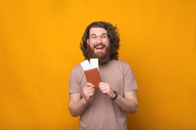 Homem barbudo hippie espantado com cabelo comprido e encaracolado mostrando passaporte e passagens