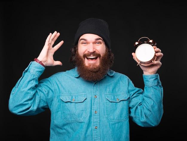 Homem barbudo hippie espantado segurando um despertador sobre um fundo escuro