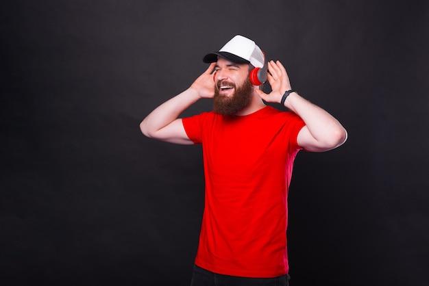 Homem barbudo hippie feliz ouvindo música em fones de ouvido sobre fundo preto