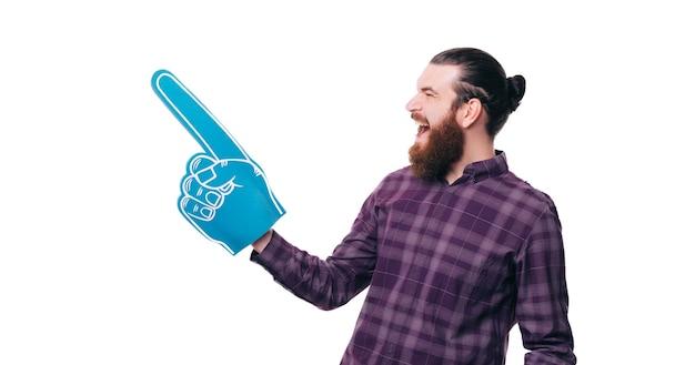 Homem barbudo hippie surpreso apontando para o canto com luva de espuma em leque