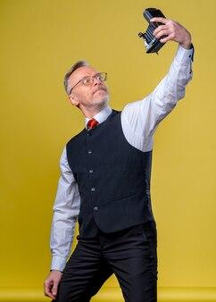 Homem barbudo idoso alegre com bigode de cabelos grisalhos e camisa isolada em um fundo amarelo