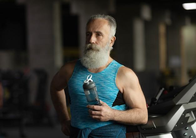 Homem barbudo idoso em uma academia. descansando após o exercício
