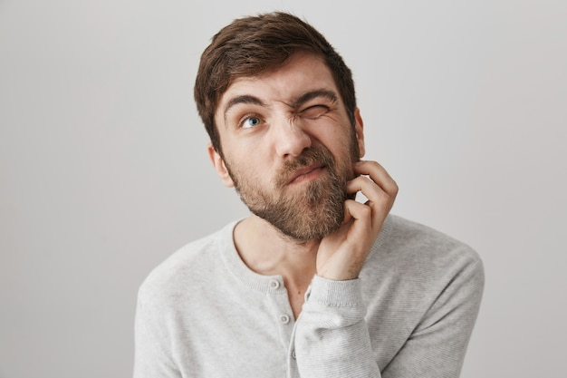 Homem barbudo indeciso pensativo coçando a barba e olhando para cima pensando