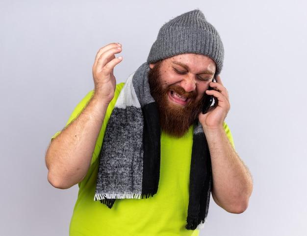 Homem barbudo insalubre com chapéu e cachecol quente no pescoço sentindo-se doente, sofrendo de gripe, falando no celular, chateado e chorando muito