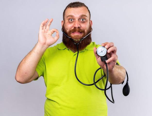 Homem barbudo insalubre em camisa pólo amarela enjoado medindo a pressão arterial usando tonômetro confuso mostrando sinal de ok em pé sobre uma parede branca