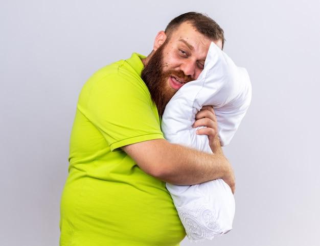 Homem barbudo insalubre em uma camisa pólo amarela se sentindo mal, segurando um travesseiro, sofrendo de gripe