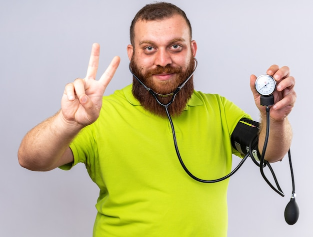 Homem barbudo insalubre em uma camisa pólo amarela se sentindo melhor medindo a pressão arterial usando o tonômetro e sorrindo mostrando o sinal v em pé sobre uma parede branca