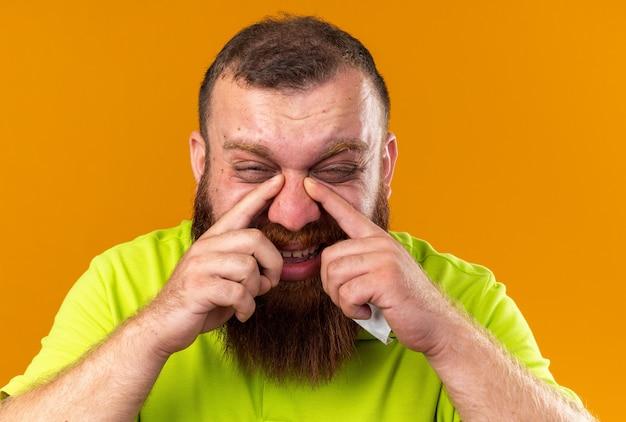 Homem barbudo insalubre em uma camisa pólo amarela se sentindo terrível, sofrendo de resfriado, com dor de cabeça devido ao nariz entupido, em pé sobre a parede laranja