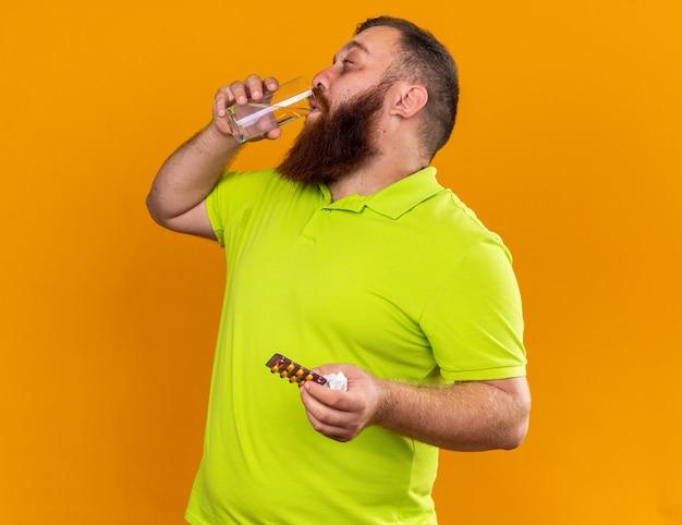 Homem barbudo insalubre em uma camisa pólo amarela segurando um copo de água e comprimidos sentindo um terrível sofrimento de resfriado tomando remédios bebendo água em pé sobre a parede laranja