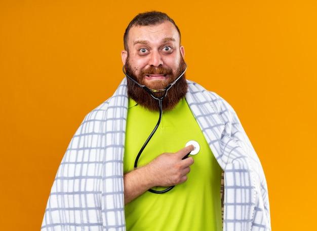 Homem barbudo insalubre enrolado em um cobertor, sentindo-se doente, sofrendo de frio, ouvindo seus batimentos cardíacos usando um estetoscópio e assustado