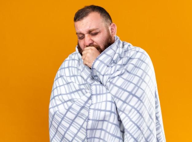 Homem barbudo insalubre envolto em cobertor, sentindo-se doente, sentindo frio, tosse
