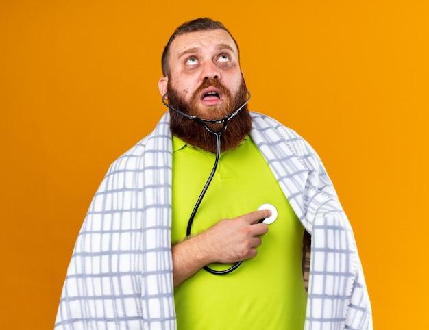 Homem barbudo insalubre envolto em cobertor, sentindo-se mal, sofrendo de frio, ouvindo os batimentos cardíacos usando um estetoscópio