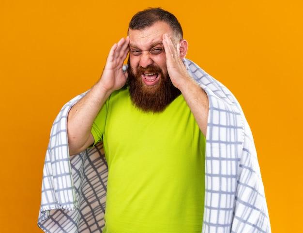 Homem barbudo insalubre envolto em cobertor, sentindo-se mal, sofrendo de frio, verificando a temperatura usando termômetro com forte dor de cabeça
