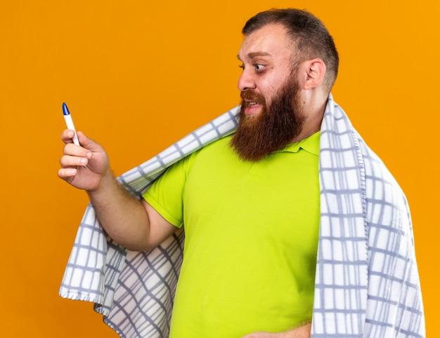 Homem barbudo insalubre envolto em cobertor sentindo-se mal, sofrendo de frio, verificando a temperatura usando termômetro e parecendo preocupado