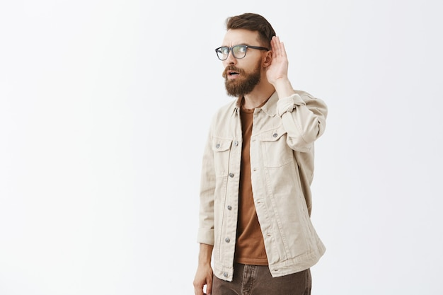 Homem barbudo intrigado de óculos posando contra a parede branca