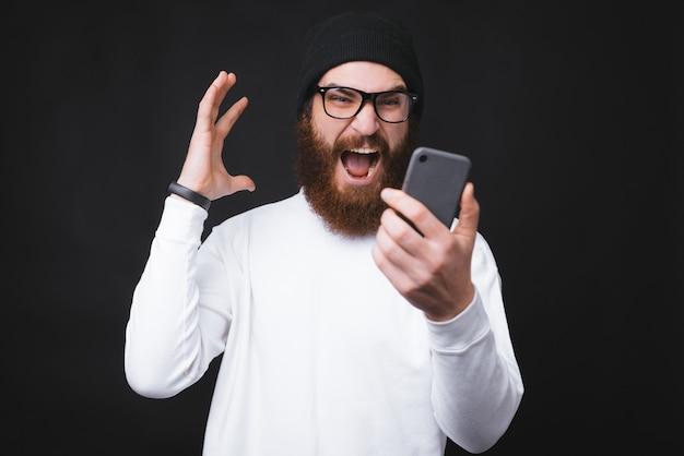 Homem barbudo irritado, gritando com smartphone em pé sobre fundo escuro